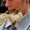 Photo of a long-haired individual holding a white flower with their teeth.