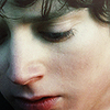 close up of Elijah Wood!Frodo Baggins' face: a bit of his curls, his left eye, nose and mouth are in the frame. his eyes are downcast, mouth open and very red. the picture is overlayed with a subtle green-to-red gradient filter