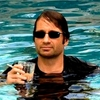 David Duchevny, fully clothed in a pool wearing sunglasses and holding a drink and cigarette