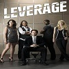 Image of the five members of the Leverage team with Nate Ford sitting in the middle, Eliot and Hardison on either side, with Parker and Sophie on the ends
