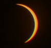 An eclipse creating the image of a rainbow crescent moon.
