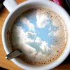 A cup of coffee with the surface photoshopped to reflect a blue sky with fluffy clouds.