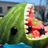 A watermelon carved in the shape of a cute shark, with its 'mouth' full of chopped fruit pieces.