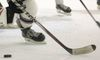closeup on hockey player's white socks with maroon stripe, with puck on stick