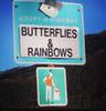 Green signpost saying Adopt-a-Highway: Butterflies & Rainbows