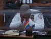 captain holy from brooklyn 99 sobbing into his hands as a gay flag rests in front of him on his desk