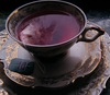 A dark and elegant tea cup filled with purple tea.