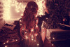 girl raising fairy lights in a dark room