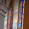Stained glass windows against beige stone.