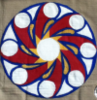 "Geometrical figure, hand-painted on beige cloth, of a round white ""sun"" with eight slanted ochre ""rays"" becoming eight red-trailed white orbs of their own, flanked by white-hot waves and smaller ochre trails against navy blue. Dubious symetry."