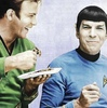 William Shatner and Leonard Nimoy dressed as kirk/Spock, but smiling and eating cake.