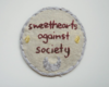 a white, circular, and handembroidered patch reading 'sweethearts against society' in maroon lettering.