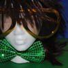 manaquin head wearing a brown wig, a sparkly green bow tie and oversized gold sunglasses against a blue and green background