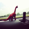 a small red and blue dinosaur perched on a car windowsill, gazing longingly into the distance wondering when her husband will return from the war