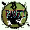 "A black cauldron on a dark green background and ink splatters. ""Riot!"" is written across it in pixelated, multicolored text"