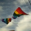 two rainbow flags with blue sky in background