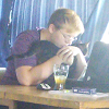 The bard in a purple hooded shirt, hugging a cat in front of a laptop with a tarot deck and a glass of kombucha next to them on the desk.