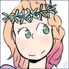 A smiling ginger-haired girl wearing a crown of flowers.