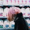 a pink-haired person, viewed from the back, looking at a shop counter with endless bottles of milk