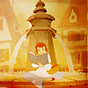 Belle from Disney's Beauty and the Beast sits reading in front of a fountain.
