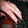 Hand with long red/black nails and a keyboard