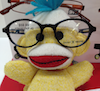 A yellow sock monkey wearing adorably large glasses