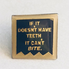 A square enamel pin reading 'if it doesn't have teeth, it can't bite', in yellow text on a dark blue background.