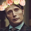 Mads Mikkelsen as Hannibal Lector wearing a flower crown.
