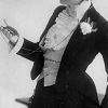 A detail of a black and white photo of Lily Elsie in Victorian male evening dress looking at a pocketwatch, 1906