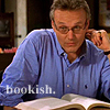 Rupert Giles sitting over a book.  Text: Bookish.