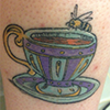 tattoo of a cup of tea with a bee perched on the rim