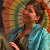 Kaylee in pilot episode of Firefly sitting in her chair with her colorful parasol temping passengers to book Serenity.