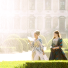 Queen Anne and Constance from The Musketeers walking in the palace gardens