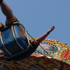 photo of someone riding a carnival swing ride, shown from below with a blue sky background