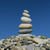 cairn of rocks in front of a blue sky - picture by John Greim