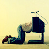 a person kneeling with their head inside the tv