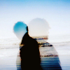double exposure silhouette of head and shoulders against blue water and sky
