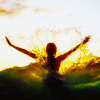 silhouette of person rising arms outstretched from green and yellow lit waves against a pale sky with a few clouds