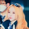 vivi from loona, she is a chinese woman with long dyed orange hair looking left