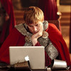 Bradley James in full Arthur Pendragon costume (armor, red cape) sitting at the round table, head in one hand, looking bored, doing something on his laptop