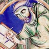 A close-up of a monk in a medieval illustration. He is leaning forward and looking at the book he is copying.