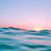 a sunset over the ocean in pastel colors