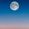 Full moon against a sunset, with a blue to pink gradient