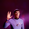Spock standing against a purple background holding up his right hand in the Vulcan salute