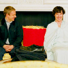 John and Sherlock sitting on a couch at Buckingham Palace