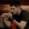 dean winchester driking coffee. he is grumpy and holds up a finger for cas to wait.