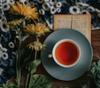 Mug of tea with flowers and book