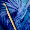 wooden crochet hook on deep blue yarn