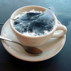 A white coffee cup and spoon on a saucer. The cup has churning water in it, like the ocean. It is all on a blue background