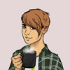 A self-portrait of a person with short brown hair holding a cup of tea and wearing a green checked flannel.